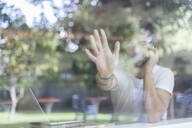 Young man with laptop on cell phone behind windowpane of a cafe raising his hand - JPTF00161
