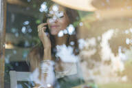 Young woman on cell phone behind windowpane of a cafe - JPTF00164