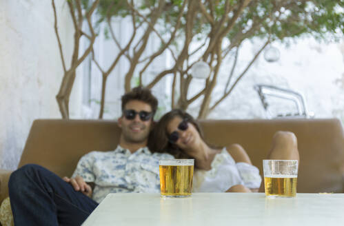 Relaxed young couple having a beer at a bar - JPTF00167