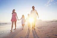 Happy family walking toward camera, holding hands, on sunny beach - JUIF01532
