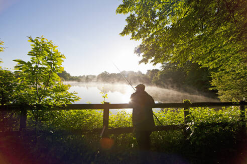 Fisherman carp fishing at dawn at fence along tranquil misty lake - JUIF01580