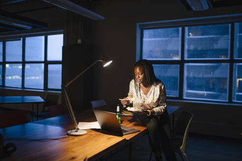 Dedicated businesswoman working late and eating sushi dinner in dark office - HEROF36634