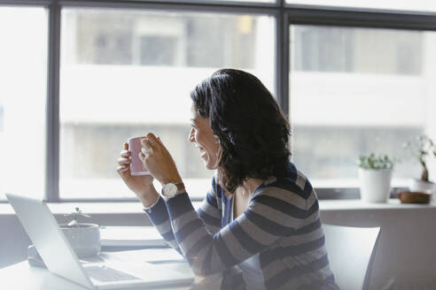 Happy businesswoman drinking coffee at laptop - HEROF36676