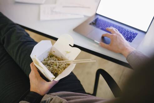 Man working late at laptop, eating take out food - HEROF36748