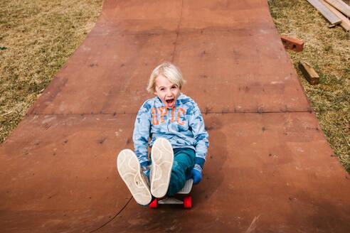 Boy sitting and skateboarding backwards down wooden skateboard ramp, portrait - ISF21546