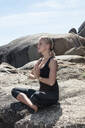 Young woman practicing lotus yoga pose on beach rock, Cape Town, Western Cape, South Africa - ISF21591