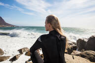 Young female surfer with long blond hair sitting on beach rock, rear view, Cape Town, Western Cape, South Africa - ISF21594