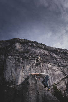 Climber bouldering in forest, Squamish, Canada - ISF21708