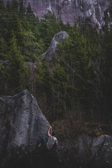 Climber bouldering in forest, Squamish, Canada - ISF21714
