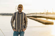 Portrait of man wearing baseball cap and striped shirt at sunset - AFVF03337
