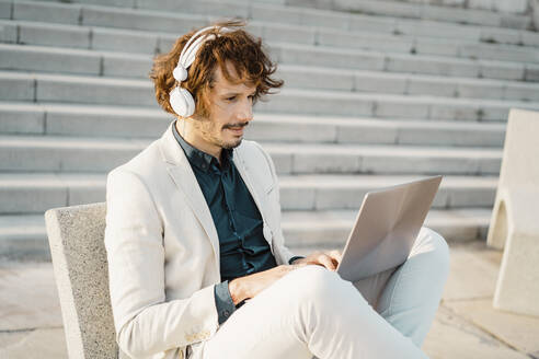 Businessman with headphones working on laptop outdoors - AFVF03379