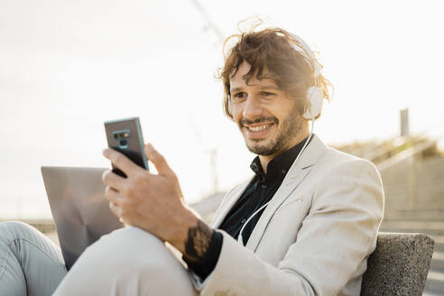 Portrait of smiling businessman with headphones and laptop looking at his mobile phone - AFVF03382