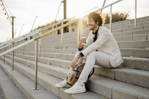 Laughing businessman with coffee to go and backpack sitting on stairs outdoors - AFVF03400