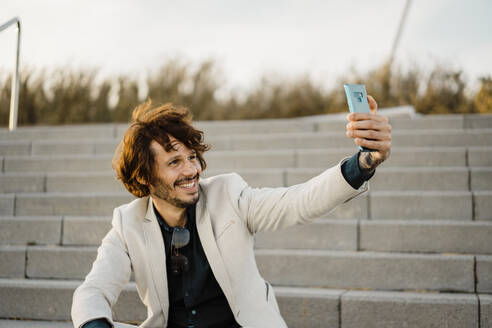 Portrait of businessman taking selfie with smartphone - AFVF03403