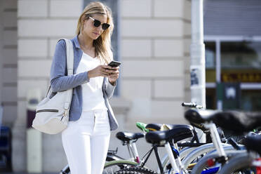 Young businesswoman texting with her mobile phone - JSRF00286