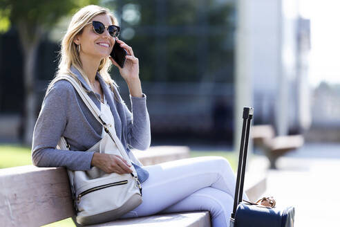 Young businesswoman talking on mobile phone while sitting in a bench - JSRF00289