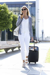 Young businesswoman talking on the smartphone with hands free while walking with suitcase - JSRF00292