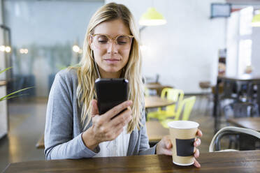 Young woman texting with her mobile phone while drinking coffee in the coffee shop - JSRF00295