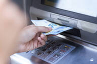 Close up of businesswoman withdraw money on a cash machine - JSRF00307