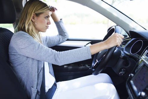 Stressed young business woman driving her car - JSRF00310