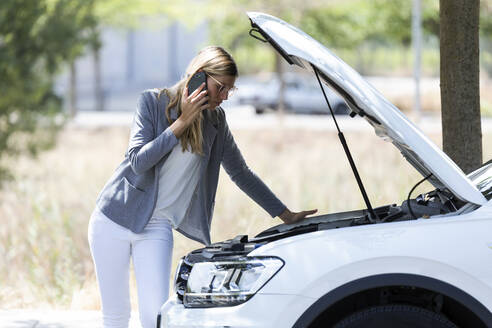 Stressed young woman calling for assistance after breaking down car - JSRF00313