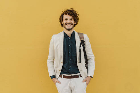 Portrait of laughing businessman with backpack standing in front of yellow wall - AFVF03411
