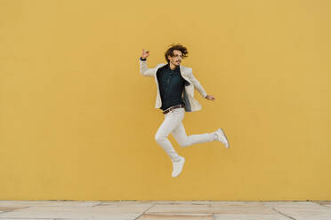 Businessman jumping in the air in front of yellow wall - AFVF03414