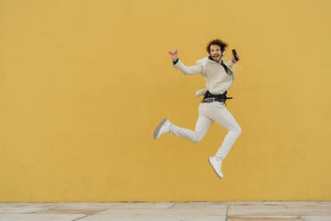 Businessman jumping in the air in front of yellow wall listening music with headphones and smartphone - AFVF03417