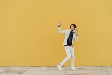 Businessman singing and dancing in front of yellow wall listening music with headphones and smartphone - AFVF03420