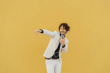 Businessman singing and dancing in front of yellow wall listening music with headphones and smartphone - AFVF03423