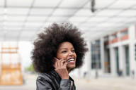 Young woman with afro hair at city train station, making smartphone call - CUF51466