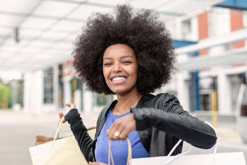 Young woman with afro hair at city train station holding up shopping bags, portrait - CUF51478