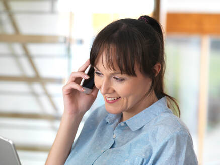 Woman smiling over the phone during a conversation at her desk - CUF51526