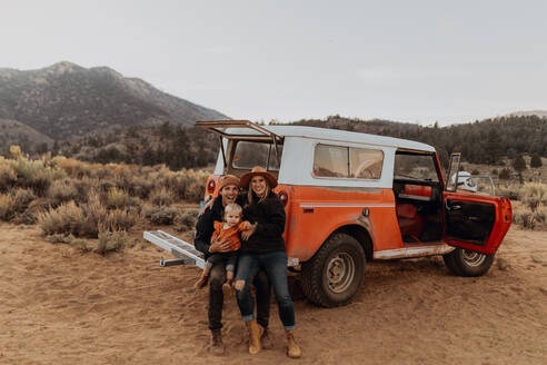 Couple with baby girl by offroad vehicle, Kennedy Meadows, California, US - ISF21776