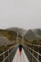 Hiker crossing suspension bridge, Wanaka, Taranaki, New Zealand - ISF21866