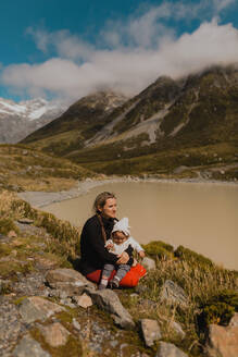 Mother with baby enjoying scenic view by lake, Wanaka, Taranaki, New Zealand - ISF21875