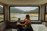 Mother and baby relaxing in motorhome, Queenstown, Canterbury, New Zealand - ISF21890
