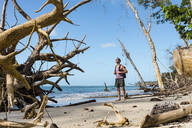 Tourist with backpack standing on a tropical beach, Cahuita National Park, Costa Rica - MAUF02608