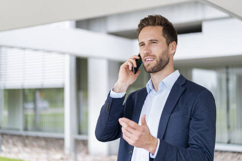 Businessman talking on cell phone outdoors - DIGF07078
