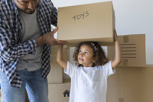 Father with daughter carrying cardboard box at new home - JPTF00174