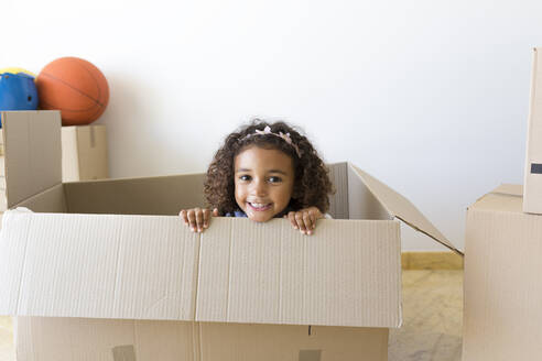 Portrait of happy girl looking out of cardboard box at new home - JPTF00180