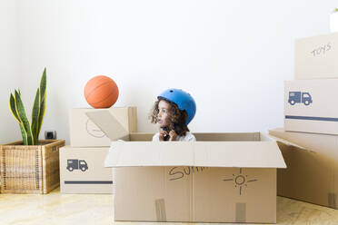 Girl inside cardboard box at new home closing bicycle helmet - JPTF00183