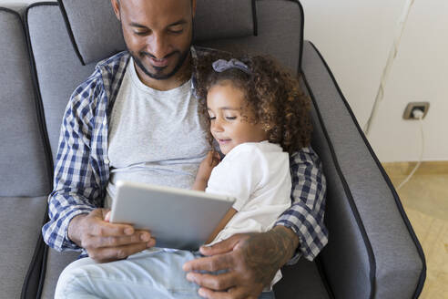 Father and daughter sitting on couch at home together looking at tablet - JPTF00189