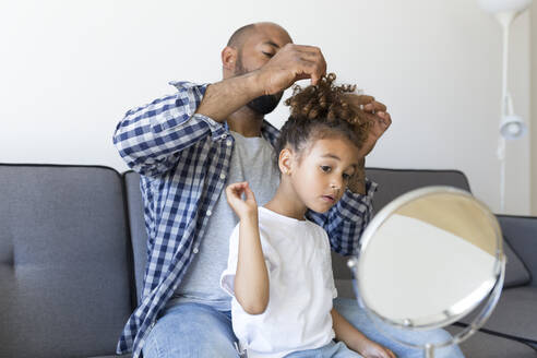 Father doing daughter's hair on couch at home - JPTF00192