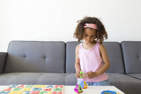 Girl playing with learning game at home - JPTF00204