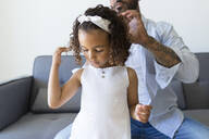 Father doing daughter's hair on couch at home - JPTF00207