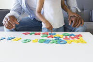 Close-up of father and daughter playing with alphabet learning game at home - JPTF00210