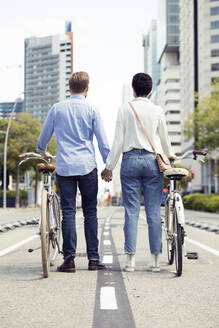 Couple with bikes in Barcelona, rear view - JSRF00345