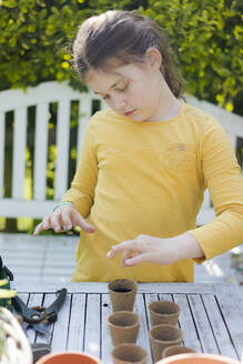 Girl with nursery pots on garden table - MOEF02265