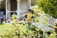 Girl gardening on garden table - MOEF02268